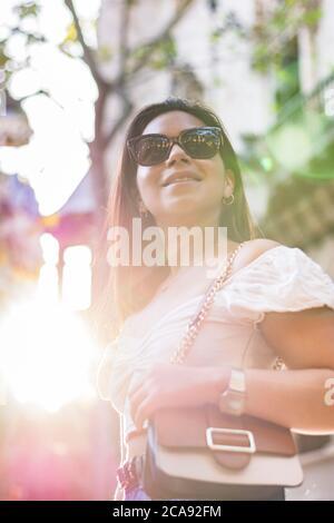Frau mit Sonnenbrille lächelt, als sie durch die Stadt geht