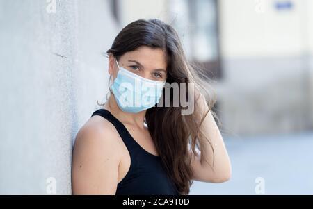 Junge Frau trägt chirurgische Maske auf Gesicht in öffentlichen Räumen. Coronavirus Verbreitung Schutzmaske Schutz gegen Influenza-Viren und Krankheiten. P - Stockfoto