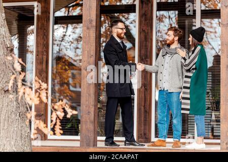 Kaukasische Paar unterzeichnen Kaufvertrag auf der Terrasse ihres neuen Hauses, junger Mann, Signatur auf dem Dokument, seine Frau, die neben Mann - Stockfoto