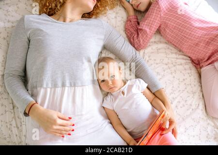 Kleines Mädchen auf die Kamera, während ihre Mutter und Schwester schlafen in den Morgen. Draufsicht Foto.