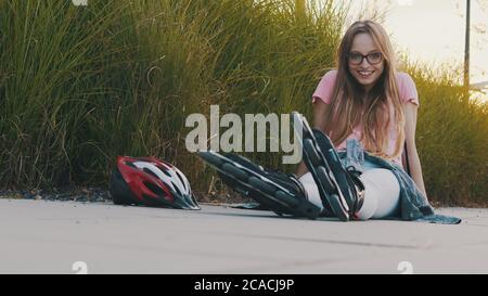 Junge kaukasische Frau sitzt auf dem Weg im Park mit Rollerblades während des Sonnenuntergangs. Sport- und Freizeitkonzept. Hochwertige Fotos - Stockfoto