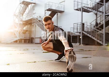 Bild von unrasierten kaukasischen Sportler in Kopfhörern, die Sport treiben, während sie im städtischen Bereich im Freien trainieren - Stockfoto