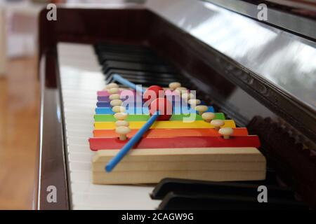 Nahaufnahme Bild von einem bunten Spielzeug Xylophon mit Schlägel auf der Tastatur eines klassischen Klaviers gesetzt. Stockfoto