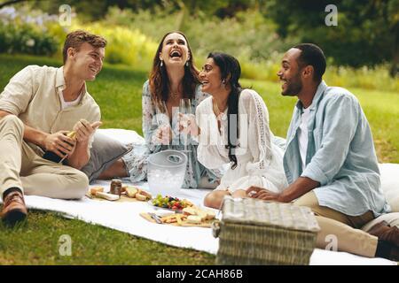Freunde verbringen Wochenende im Park und Spaß haben. Multiethnische Menschen genießen Picknick im Park. - Stockfoto