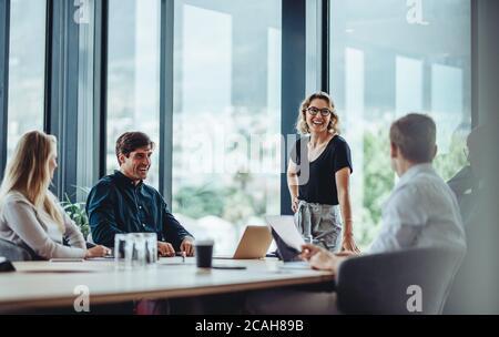 Bürokollegen, die während der Besprechung im Konferenzraum eine lockere Diskussion führen. Eine Gruppe von Männern und Frauen, die im Konferenzraum sitzen und lächeln. - Stockfoto