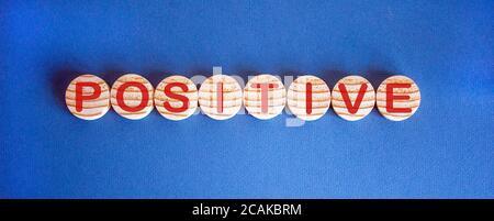 Das Wort 'positiv' auf Holzkreisen auf blauem Tisch. Schöner Hintergrund, Kopierbereich. - Stockfoto