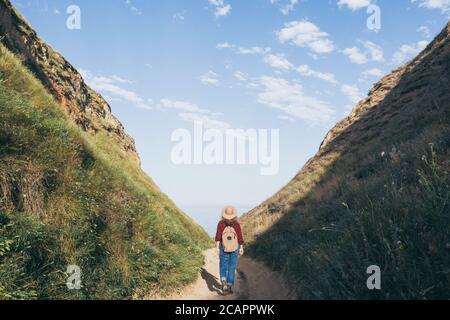 Frau mit Rucksack Wandern in der Bergschlucht mit Blick auf die Meer