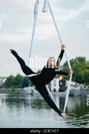 Frau Aerialistin führt Gymnastik gespalten auf hängenden Luft Seide vor dem Hintergrund des Flusses, Himmel und Bäume. - Stockfoto