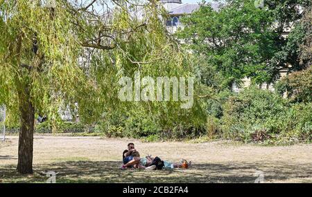 Brighton UK 10. August 2020 - Dieses junge Paar findet Schatten unter einem Baum in Pavilion Gardens Brighton an einem heißen, sonnigen Tag, wenn die Temperaturen in Teilen des Südostens wieder bis in die 30er Jahre reichen : Credit Simon Dack / Alamy Live News