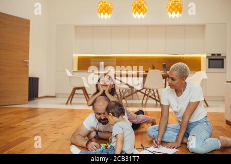 Familie Spaß zusammen im Wohnzimmer des Hauses. Mama, Papa und zwei Kinder auf dem Boden Zeichnung, lachen, spielen. Happy Family Konzept Stockfoto