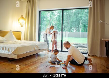 Panoramafenster im Zimmer. Junge Eltern mit ihren Kindern im Zimmer. Mutter und Tochter, Vater mit Sohn, der auf dem Boden spielt. Wachsende Generation, Familie