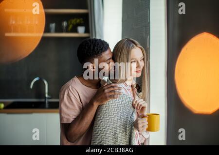 Schönen afrikanischen Kerl küsst seine kaukasischen Freundin am Hals von hinten, zu Hause in der Küche Zimmer mit modernem Interieur - Stockfoto