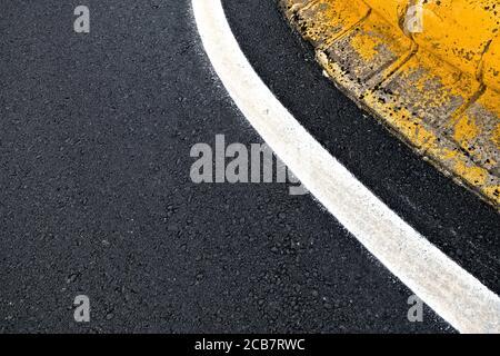 Straßenbeschilderungs-Details, geschwungenes weißes reflektierendes Band an einem Kreisverkehr.