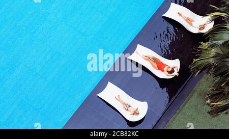 Junge Mutter und Kinder entspannen sich auf den Sonnenliegen am Swimmingpool im luxuriösen Spa-Resort oder in der Villa. Draufsicht. Tourismus-Industrie Krise nach covid 19 Coronavirus pand - Stockfoto