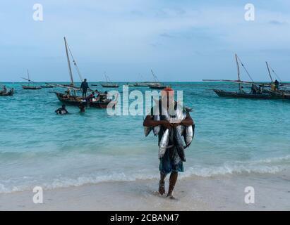 Nungwi, Sansibar, Tansania, Afrika - Januar 2020: Schwarzer Afrikaner trägt Thunfisch auf dem Street Fish Market im Dorf Nungwi, die Menschen sind es