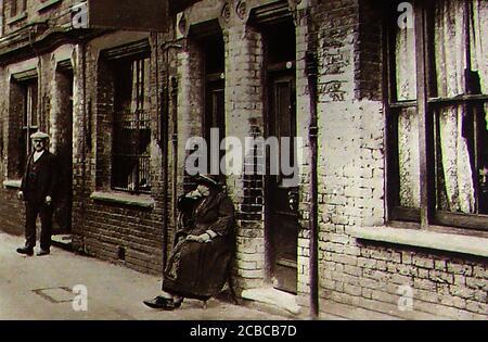 Slum Wohnungen und Back to Back Häuser in Großbritannien um 1940. Eine alte Frau sitzt auf einem Stuhl neben ihrer Tür, von einem männlichen Nachbarn mit flacher Kappe betrachtet. Ganz rechts guckt ein gespenstisches Gesicht durch die Vorhänge. - Stockfoto