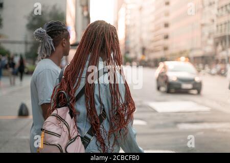 Ein schwarzes Paar, das an einer Straße in der Stadt steht und darauf wartet, sie zu überqueren.