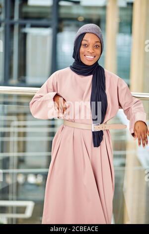 Mode Schuss von glamourösen afrikanischen Frau im muslimischen Stil gekleidet Rosa Kleid mit modernen Hut posiert in leeren Halle - Stockfoto