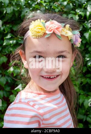 Kopf- und Schulterportrait eines 4-jährigen weißen Mädchens, lächelnd, mit künstlichen Blumen im Haar. Lancashire, England, Großbritannien