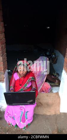 DISTRIKT KATNI, INDIEN - 20. AUGUST 2019: Ein indisches Dorf arme Frau, die Laptop betreibt, Konzept für asiatisches weibliches digitales Lernen. - Stockfoto