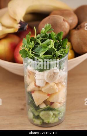 Glas leckeren Joghurt mit Minze und frischen Erdbeeren, Banane, Kalk, Nektarine in einem Weidenkorb auf einem Holztisch - Stockfoto