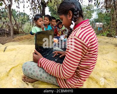 DISTRIKT KATNI, INDIEN - 01. JANUAR 2020: Indisches Dorf arme Mädchen Betrieb Computer mit Gruppe von Kindern, Konzept für digitale Technologie Bewusstsein. - Stockfoto