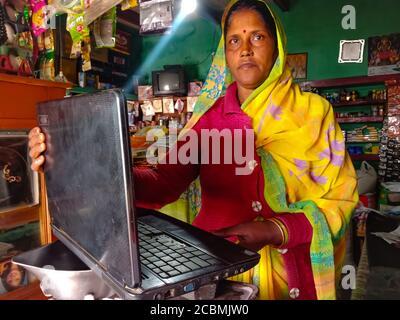 DISTRIKT KATNI, INDIEN - 01. JANUAR 2020: Eine indische Ladenbesitzerin, die Laptop-Technologie am Ladentisch für Abrechnungszwecke betreibt. - Stockfoto