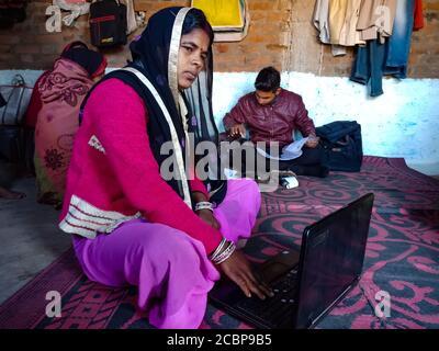 DISTRIKT KATNI, INDIEN - 25. JANUAR 2020: Eine indische Dorffrau, die zu Hause Laptop-Technologie betreibt, Konzept für digitales Bewusstsein. - Stockfoto