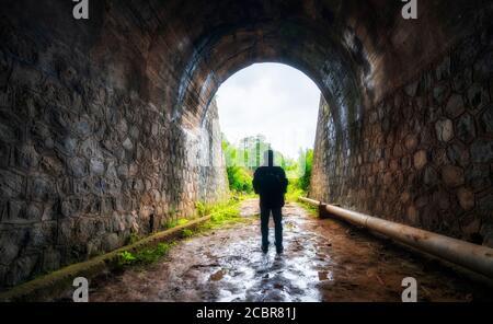 Silhouette Reisende Mann in der alten Eisenbahntunnel erforscht, verlassene Architektur des 19. Jahrhunderts bis heute in der Nähe von Da Lat, Vietnam