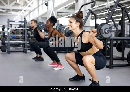 Sportliche Menschen, multiethnische Gruppe führen Übungen mit schweren Gewichten in der Turnhalle. Junge verschiedene Männer und Frauen Training, haben muskulösen Körper