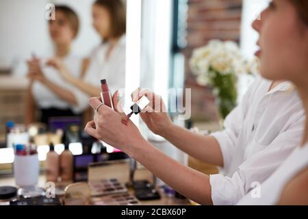 Nahaufnahme der Hand eines professionellen Make-up-Künstlers mit Lippenstift Studenten im Meisterkurs