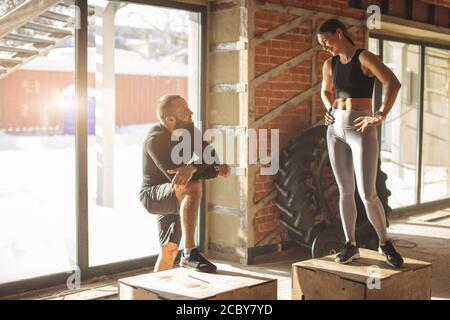 Kaukasische bärtige Fitness-Trainer gibt Ratschläge für junge lächelnde fit Frau. Sportler sprechen freundlich in einem modernen Fitnessraum mit Crossfit-Ausrüstung.