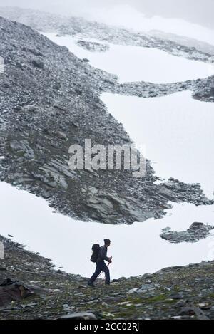 Wandermännchen mit Rucksack und Wanderstöcken wandern in verschneiten Bergen. Junge Rucksacktouristen, die auf einem felsigen Hügel spazieren und auf schneebedeckte Felsen blicken. Konzept von Reisen, Wandern und Bergsteigen. Stockfoto