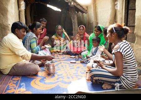Bhagwanti Devi (55, 4. V.l.) isst mit ihrer Familie zu Hause in Bihar, Indien. Im Rahmen ihrer Teilnahme am LWR's Transboundary Flood Resilience Project hat sie neue landwirtschaftliche Techniken erlernt, die es ihrer Familie ermöglicht haben, außerhalb der Saison Feldfrüchte zu bewirtschaften, sowie neue Wege, ihre landwirtschaftlich basierte Lebensgrundlage zu diversifizieren, um sie weniger anfällig für Schocks bei starken Regenfällen und Überschwemmungen zu machen. Transboundary Flood Resilience Project 2. Dezember 2019 - West Champaran District, Bihar State, Indien. Foto von Jake Lyell für Lutheran World Relief. - Stockfoto