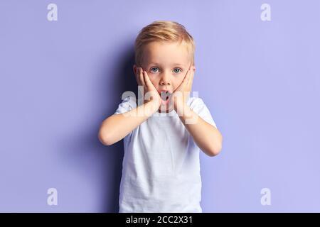 Schöne blauäugige Junge Kind überrascht, stehen mit geöffnetem Mund Blick auf die Kamera. Isolierte lila Hintergrund