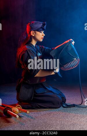kaukasischen Kendo Kämpfer sitzen auf dem Boden vor dem Kampf, tragen spezielle Kendo Kleid und mit allen Geräten, Bambus Schwert Shinai. japanische Martial A