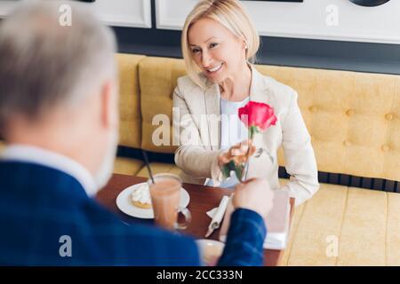 Mann gibt eine Rose zu einer blonden schönen lächelnden Frau, Glück, Überraschungskonzepte. Close up photo.celebration Konzept