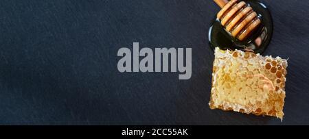 Bio-Honig und rustikales Brot auf einem dunklen Stein Hintergrund. Gesundes Frühstück. - Stockfoto