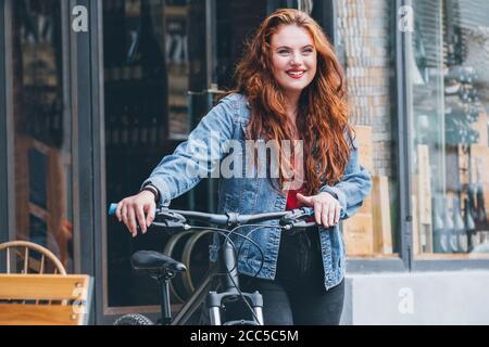Porträt von lächelnden roten gewellten langen Haaren kaukasischen Frau auf der Straße der Stadt zu Fuß mit einem Fahrrad. Natürliche Menschen Schönheit Konzept Bild. Stockfoto