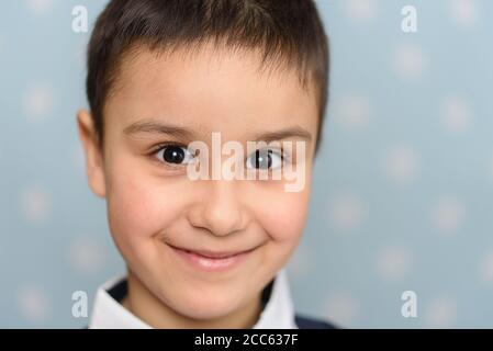Kopf Und Schultern Portrait Des Hübschen Jungen. Glücklicher 6-jähriger europäischer Junge, der über blauem Studiohintergrund posiert. Kind mit großem Lächeln. Kopfschuss o - Stockfoto