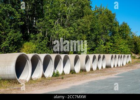 Eine Reihe von Betonrohren neben einer Straße. Dies ist der Rohrtyp, der für Kanalisation verwendet wird. Bäume und blauer Himmel im Hintergrund. - Stockfoto