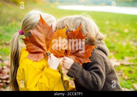 Glückliche Kinder mit Herbstblatt küssen im Park.