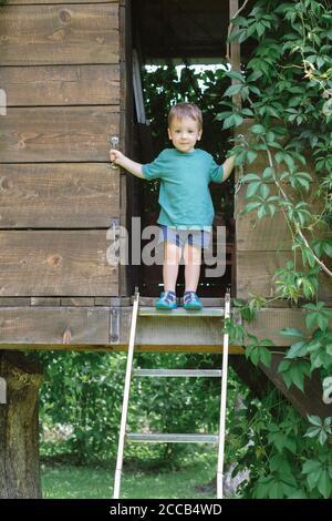 Kleiner Junge steht auf Treppe auf Baumhaus im grünen Garten. Sommerzeit