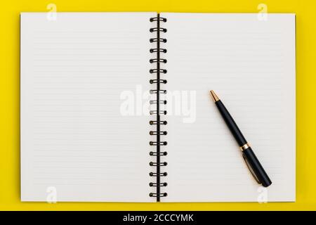 Business Copy Space, Luxus Spiral Open Notebook mit leeren Seiten und Stift auf gelbem Hintergrund, Draufsicht - Stockfoto