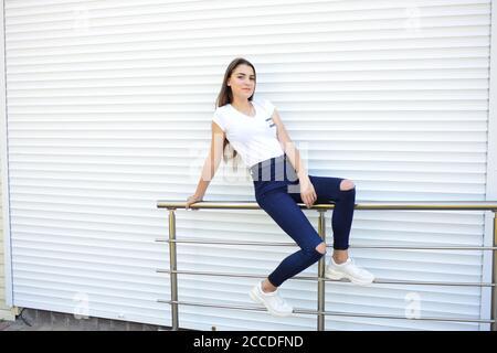 Schöne junge Frau trägt Jeans, weißes T-Shirt, auf der Straße stehen. Foto in der Nähe von Eisenzaun - Stockfoto