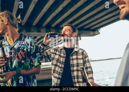 Gruppe von Freunden feiern, ausruhen, Spaß haben und Party im Sommer Tag. Junge Männer trinken Bier, reden, lachen. Schauen Sie glücklich und fröhlich. Festliche Zeit, Feiertag, Sommerzeit, Einheit und Freundschaft.