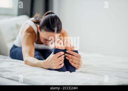 Schlanke kaukasische sportliche Frau macht Übungen auf dem Bett zu Hause, junge Dame Stretching am Morgen, gesunde Lebensweise Konzept