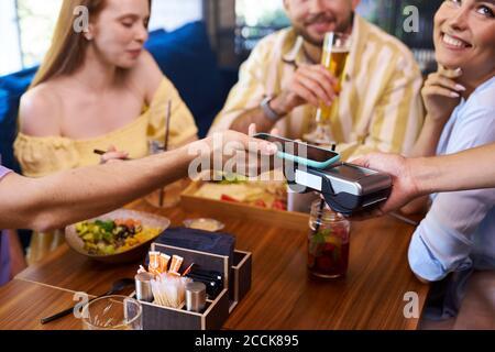 Kunden zahlen für die Mahlzeit per Smartphone, im Restaurant. Kontaktloses Zahlungskonzept - Stockfoto