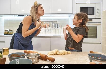 Mutter und Tochter spielen mit Pizzateig in der Küche bei Zu Hause Stockfoto