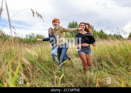 Sommerferien Urlaub glückliche Menschen Konzept. Gruppe von drei Freunden Junge und zwei Mädchen laufen und Spaß zusammen im Freien haben. Picknick mit Freunden auf dem Weg in die Natur